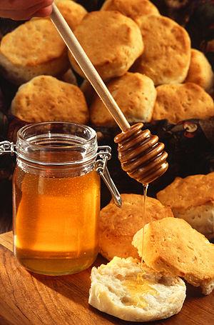 A jar of honey with honey dipper
